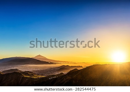 Sun with sunlight over mountains on blue sky with haze and Teide volcano on background at evening sunset in Tenerife Canary island, Spain at spring or summer
