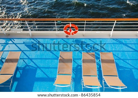sunbath chairs on side of cruise liner - stock photo