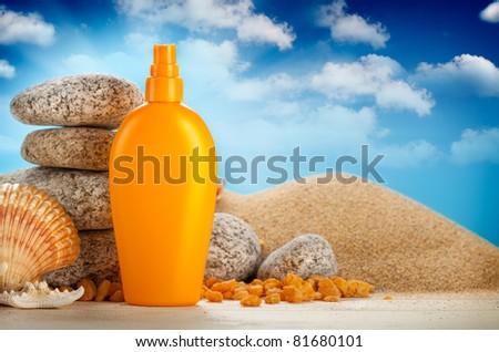 Sunbath - suntan oil on beach - stock photo
