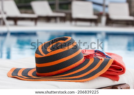 Sunbathing accessories. Sunbathing accessories on beach towel by a swimming pool - stock photo