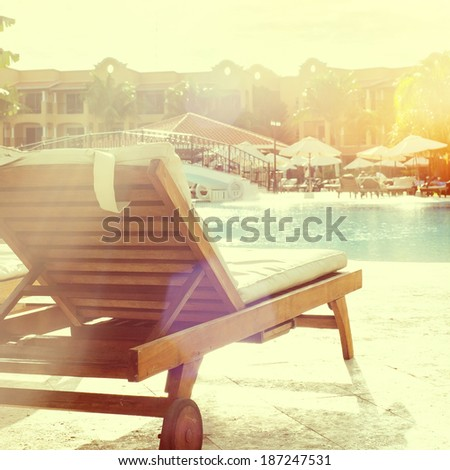 Sunbathing chair at a resort pool, instagram style - stock photo