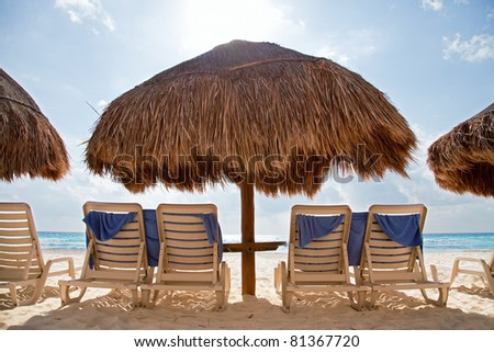 Sunbathing chairs in front of the blue ocean. - stock photo