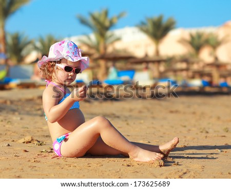 Sunbathing kid girl in hat sitting on sand and looking - stock photo