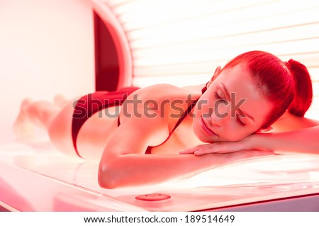 Sunbathing on tanning bed. Beautiful young woman lying on tanning bed and keeping eyes closed - stock photo