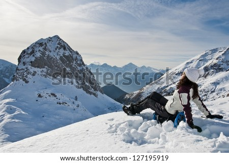 Sunbathing on the snow (B): A girl sunbathing and relaxing on the top of a mountain in the Italian Alps after a strenuous hike with snow shoes. - stock photo