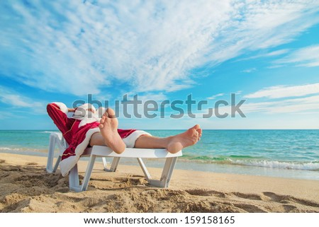 sunbathing Santa Claus relaxing in bedstone on tropical sandy beach - Christmas concept - stock photo