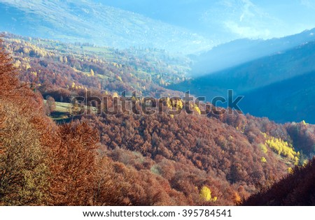 Sunbeam and autumn misty mountain view with colorful trees on slope. - stock photo