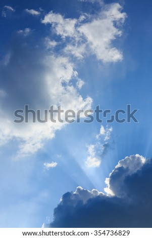 sunbeam of sunlight through clouds on clear blue sky - stock photo