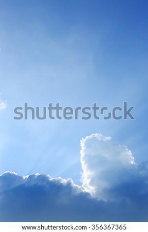 sunbeam of sunlight through clouds on clear blue sky - stock photo