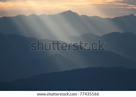Sunbeam over mountain - stock photo