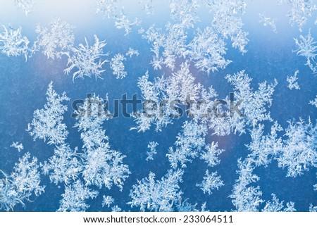 sunbeam spots and frosty pattern on window pane at winter dawn - stock photo