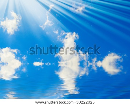 Sunbeams and clouds on blue sky above sea. - stock photo