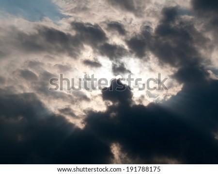 Sunbeams breaking through clouds - stock photo