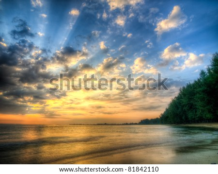 Sunbeams bursting through low altitude clouds, accumulated over the night, which are warming up and dispersing, but obscuring the rising sun at this moment early in the morning. - stock photo