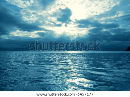 Sunbeams coming out of the sky above the sea surface - stock photo