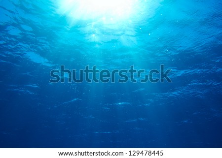 Sunbeams in the blue water - stock photo