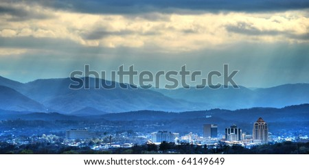Sunbeams on the city- The sun cuts through the clouds over the city of Roanoke, VA - stock photo
