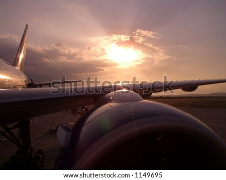 SUNBEAMS ON THE WING. Sun over aeroplane wing at an airport in late afternoon. - stock photo