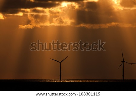 Sunbeams over a wind farm offshore Llandudno North Wales UK - stock photo