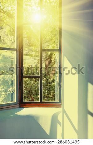 Sunbeams passing through vintage window into room - stock photo