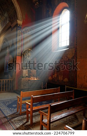 Sunbeams passing through window to wooden benches in Armenian church of Lviv with warm tones  - stock photo