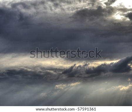 Sunbeams pierce the evening clouds - stock photo