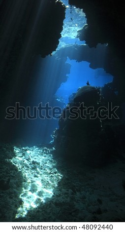 sunbeams shining through an underwater cave