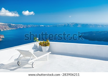 Sunbed on the terrace of a hotel. Santorini island, Greece. Beautiful summer landscape with sea view - stock photo
