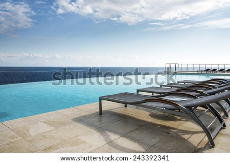 Sunbed's by an Infinity pool - stock photo