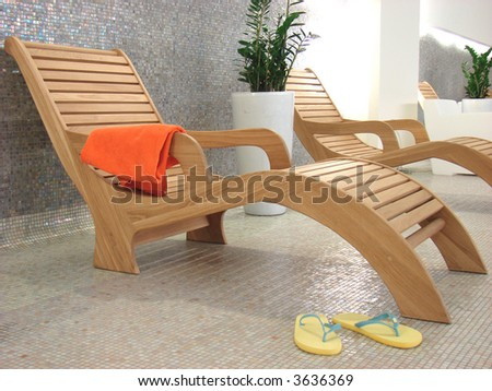 sunbed with orange towel and  sandals flipflop in the swimming pool plant behind - stock photo