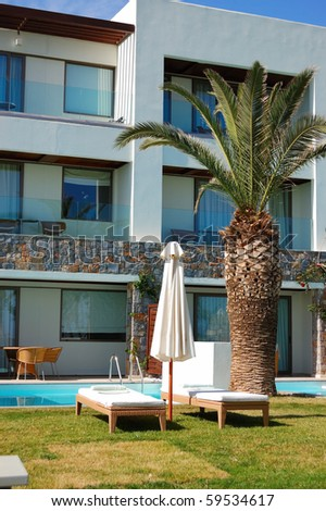 Sunbeds and palm tree  at swimming pool of luxury hotel, Crete, Greece - stock photo