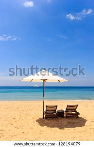 Sunbeds and umbrella on a tropical beach - stock photo