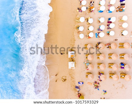 Sunbeds and umbrellas bird's eye view on sand beach in Greece