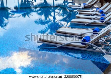 Sunbeds beside swimming pool tropical beach resorts - stock photo