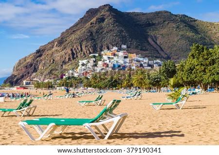Sunbeds of Playa de las Teresitas beach and San Andres village on background, Tenerife, Spain - stock photo