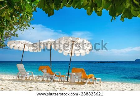 Sunbeds with orange towels under white umbrellas on sandy beach, Phi Phi Island, Phuket area, Thailand - stock photo