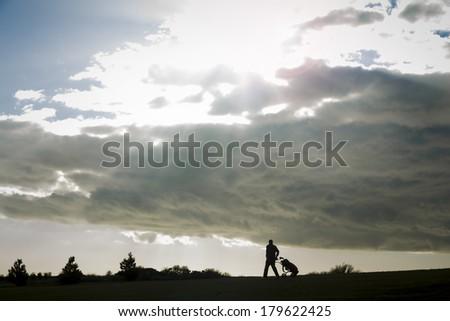 Sunburst and golfer - stock photo