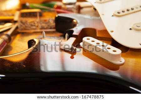 Sunburst electric guitar body on guitar repair desk. Electric guitar on a guitar repair work shop desk.  Double cutaway solid body guitar, sunburst color. Shallow depth of field.  - stock photo