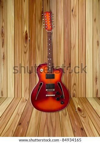 sunburst electric guitar on wood background - stock photo