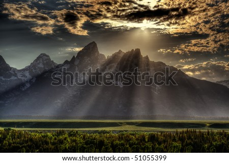 Sunburst through clouds at sunset over Tetons mountain range, Grand Teton National Park - stock photo
