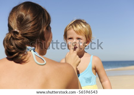 Suncare on the beach: Mother applying sunscream to her daughter - stock photo