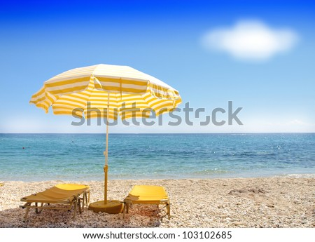 Sunchairs and umbrella on Carribean Beach - stock photo