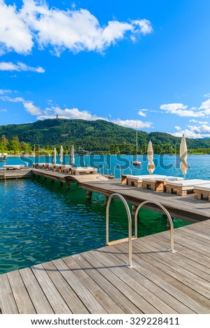 Sunchairs on wooden pier and view of beautiful alpine lake Worthersee in summer, Austria - stock photo