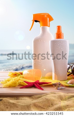Suncream on towel and wooden slats with shells. Sun shine and sea background. Vertical composition. Front view - stock photo