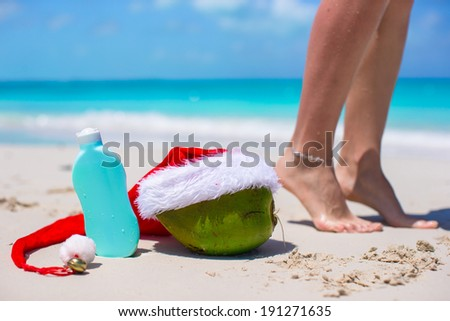 Suncream, Santa Hat on coconut and tanned female legs at white beach - stock photo