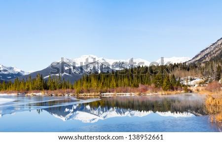 Sundance Mountain range reflected on Lake Vermilion, Banff National Park, Canada. - stock photo