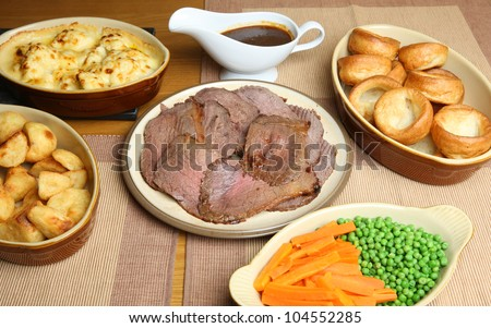 Sunday roast beef dinner in serving dishes - stock photo