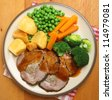 Sunday roast pork dinner with vegetables and gravy. - stock photo