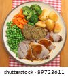 Sunday roast pork dinner with vegetables, stuffing and gravy. - stock photo