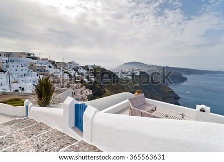 Sundeck with armchairs and table in front of Caldera view in Santorini island